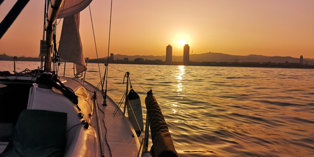 Sailing by Christopher Cross during sunset sail. Barcelona sky line during sunset sail.