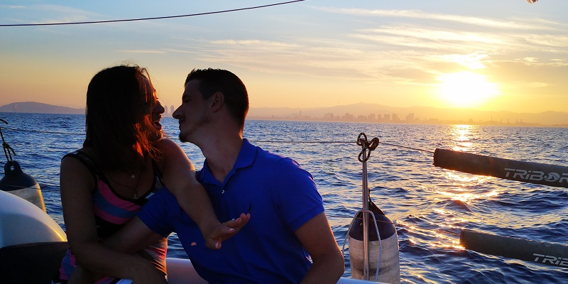 Propose on a sail boat with the sunset